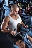 Hombre que hace entrenamiento con la máquina del tirón-abajo Foto de archivo