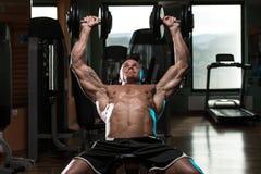 Hombre que hace entrenamiento de la prensa de banco de pendiente de la pesa de gimnasia Imagenes de archivo