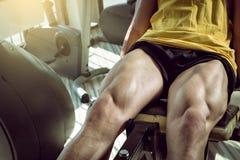 Hombre que hace la extensión de la pierna en gimnasio Fotografía de archivo