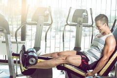 Hombre que hace la extensión de la pierna en gimnasio fotos de archivo libres de regalías