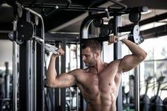 Hombre que hace la mosca del cable en gimnasio Fotografía de archivo