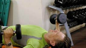 Hombre que hace la prensa de banco con pesas de gimnasia en estudio de la aptitud almacen de metraje de vídeo