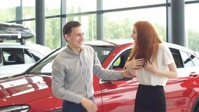 Hombre que hace la sorpresa para su esposa, comprándola un nuevo coche en la representación almacen de video