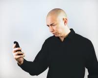 Hombre que hace muecas en Smartphone Fotos de archivo