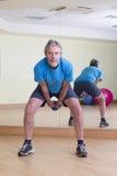 Hombre que hace oscilaciones de la pesa de gimnasia Imagen de archivo