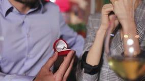 Hombre que hace propuesta de matrimonio a la mujer en primer del restaurante metrajes