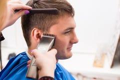 Hombre que hace que el pelo sea cortado por el estilista en salón Fotos de archivo libres de regalías