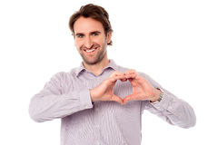 Hombre que hace símbolo del corazón con las manos imagen de archivo