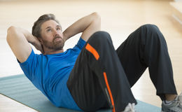 Hombre que hace Sentar-UPS en la estera del ejercicio Imagenes de archivo