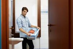Hombre que hace tareas con la lavadora Imagenes de archivo