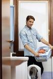 Hombre que hace tareas con la lavadora Foto de archivo