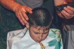 Hombre que hace a un adolescente del muchacho del corte de pelo Imágenes de archivo libres de regalías