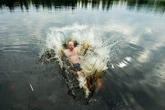Hombre que hace un chapoteo en un lago Foto de archivo libre de regalías