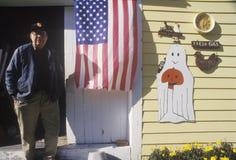 Hombre que hace una pausa la bandera americana colgada en su hogar, Nueva Inglaterra Foto de archivo