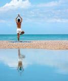 Hombre que hace yoga. Actitud de Vrikshasana (el árbol) Foto de archivo libre de regalías