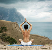 Hombre que hace yoga en el mar y las montañas fotografía de archivo