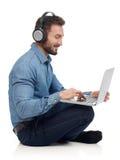 Hombre que hojea en el ordenador portátil Fotos de archivo