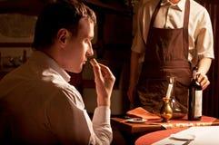 Hombre que huele el corcho de un vino Foto de archivo libre de regalías