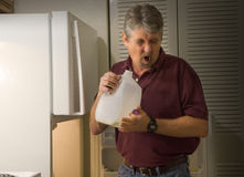 Hombre que huele la leche amarga putrefacta estropeada Imagenes de archivo