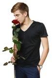 Hombre que huele la rosa roja Imágenes de archivo libres de regalías