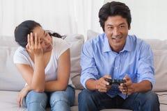 Hombre que ignora a su novia que juega a los videojuegos Fotos de archivo