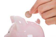 Hombre que inserta la moneda en Piggybank Imagen de archivo libre de regalías