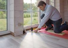 Hombre que instala el nuevo piso de madera laminado fotos de archivo libres de regalías