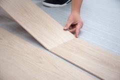 Hombre que instala el nuevo piso de madera laminado fotografía de archivo libre de regalías