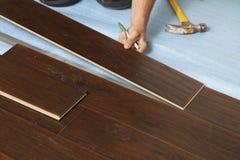 Hombre que instala el nuevo suelo de madera laminado fotos de archivo