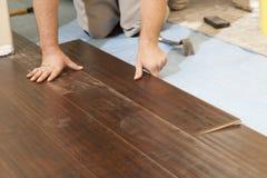 Hombre que instala el nuevo suelo de madera laminado fotografía de archivo