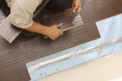 Hombre que instala el nuevo suelo de madera laminado imagen de archivo libre de regalías