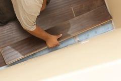 Hombre que instala el nuevo suelo de madera laminado fotografía de archivo libre de regalías