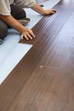 Hombre que instala el nuevo suelo de madera laminado fotos de archivo libres de regalías
