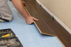 Hombre que instala el nuevo suelo de madera laminado foto de archivo