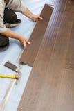 Hombre que instala el nuevo suelo de madera laminado imagenes de archivo