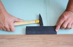 Hombre que instala el nuevo suelo de madera laminado Trabajador que instala el suelo laminado de madera con el espacio de la copi fotos de archivo libres de regalías