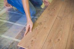 Hombre que instala el nuevo suelo laminado de madera calor infrarrojo del piso imagen de archivo