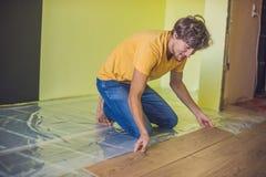 Hombre que instala el nuevo suelo laminado de madera calor infrarrojo del piso fotografía de archivo