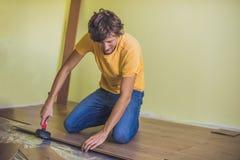 Hombre que instala el nuevo suelo laminado de madera calor infrarrojo del piso imagen de archivo libre de regalías