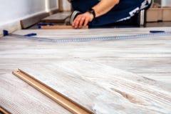 Hombre que instala el nuevo suelo laminado de madera en casa fotografía de archivo