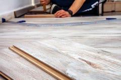 Hombre que instala el nuevo suelo laminado de madera en casa foto de archivo libre de regalías