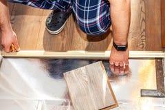 Hombre que instala el nuevo suelo laminado de madera en casa imagenes de archivo