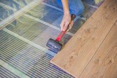 Hombre que instala el nuevo suelo laminado de madera sistema de calefacción infrarrojo de piso debajo del piso laminado imágenes de archivo libres de regalías