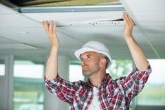 Hombre que instala el techo suspendido en casa fotografía de archivo