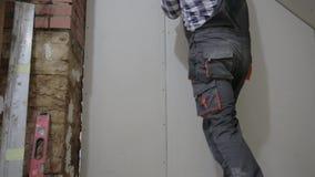 Hombre que instala la hoja del cartón yeso para emparedar para la construcción del sitio del ático almacen de video