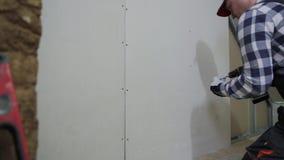 Hombre que instala la hoja del cartón yeso para emparedar para la construcción del sitio del ático almacen de metraje de vídeo