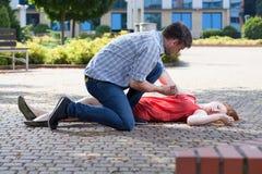 Hombre que intenta ayudar a la mujer inconsciente Imágenes de archivo libres de regalías