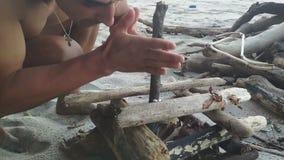 Hombre que intenta conseguir el fuego por concepto prehistórico de la vieja manera metrajes