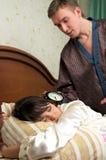 Hombre que intenta despertar a su esposa Fotos de archivo
