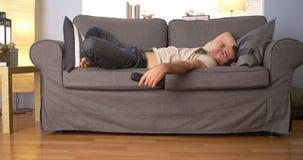 Hombre que intenta dormir en el sofá Imágenes de archivo libres de regalías